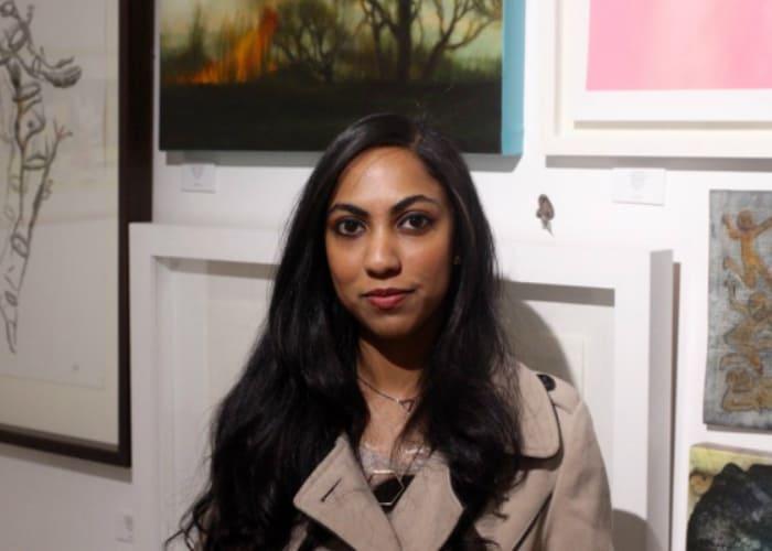 """Il giovane curatore Shenaz Mahomed è in piedi di fronte alla mostra """"Giovani collezionisti""""."""