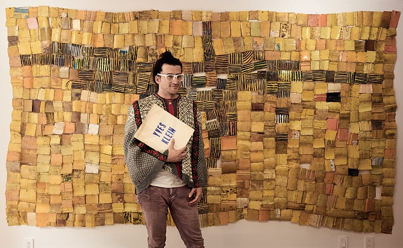 Andrew Berardini standing in front of a work by Serge Attukwei Clottey at Leadapron. Los Angeles, CA. © Stefan Simchowitz.