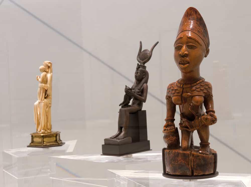 Escultura francesa medieval de la Virgen María y el Niño (izquierda) Iris amamantando a su hijo Horus (centro), figura de maternidad del siglo XIX de la cultura Yombe del Congo (derecha). Parte de la exhibición The Great Vestibule