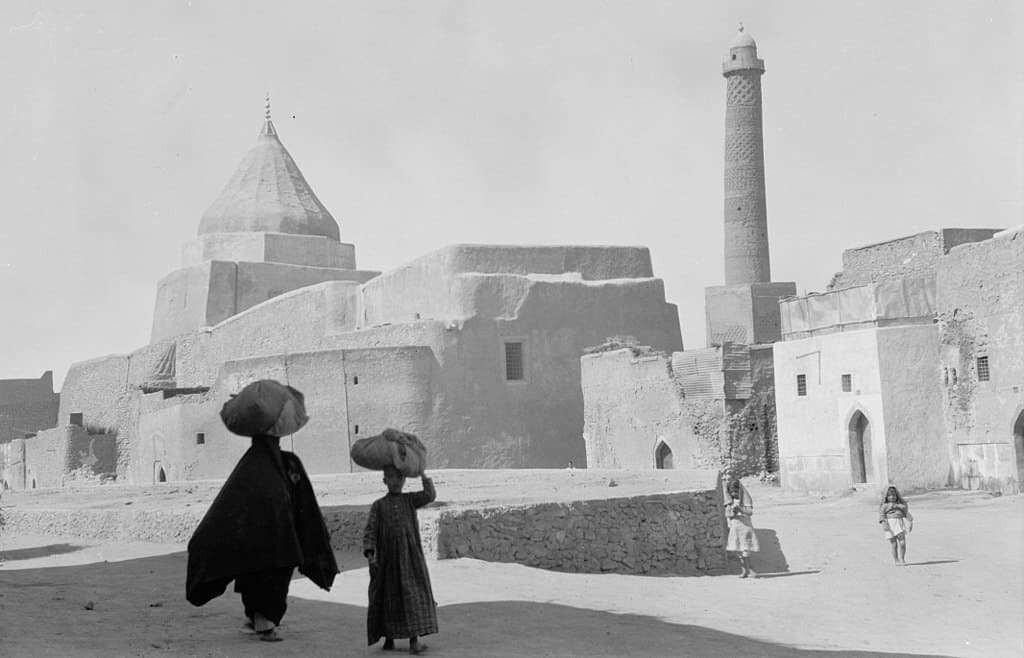 Iraq. Mosul. In the heart of ancient Mosul, showing a Yezidi shrine to the left and the Nouri Mosque minaret to the right. 1932. Courtesy of Wikimedia Commons.