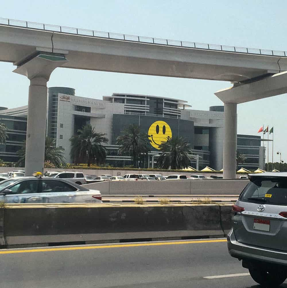 Happiness Police. An enormous smiling face looks out across Dubai from a government police building, April 2017. Photographer: Zaekr211, reddit user.