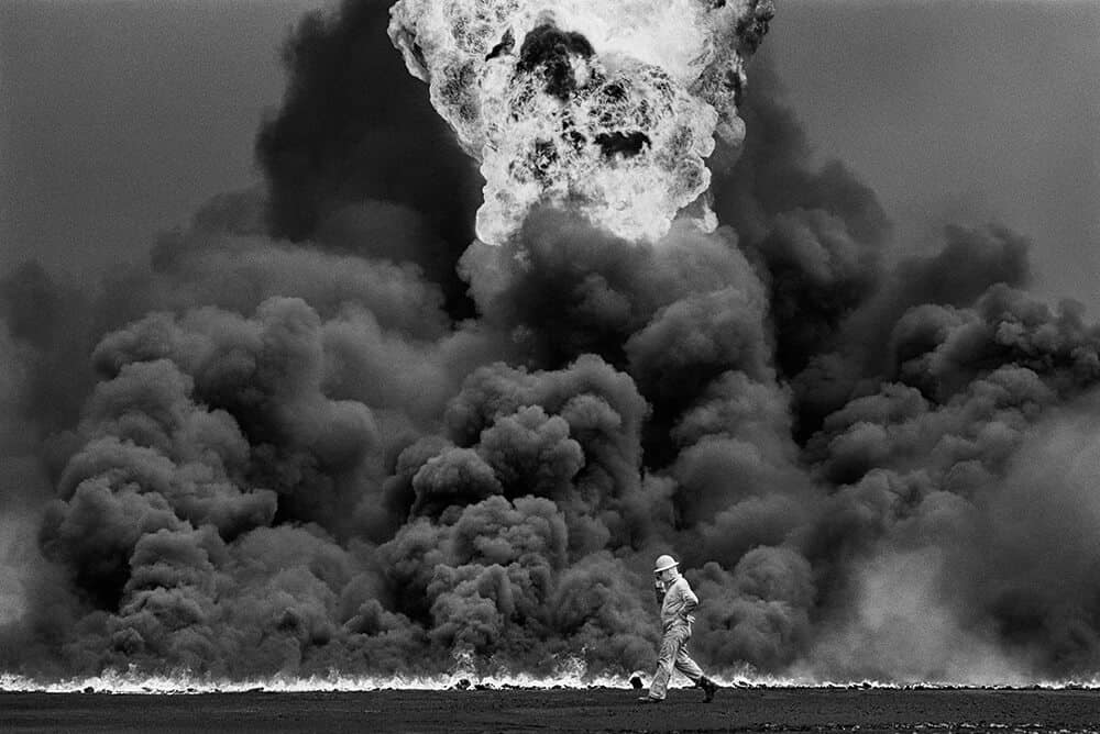 "Following the devastation of Kuwait's oil fields by Saddam Hussein's retreating forces in 1991, Brazilian photographer Sebastião Salgado travelled to Kuwait to photograph the inferno. Some 700 oil wells and an unspecified number of oil-filled low-lying areas were set alight, causing one of the worst environmental disasters in living memory. Salgado wrote that ""in all [his] long life, [he] never again found this kind of light – it was a Dantesque night."" © Sebastião Salgado"