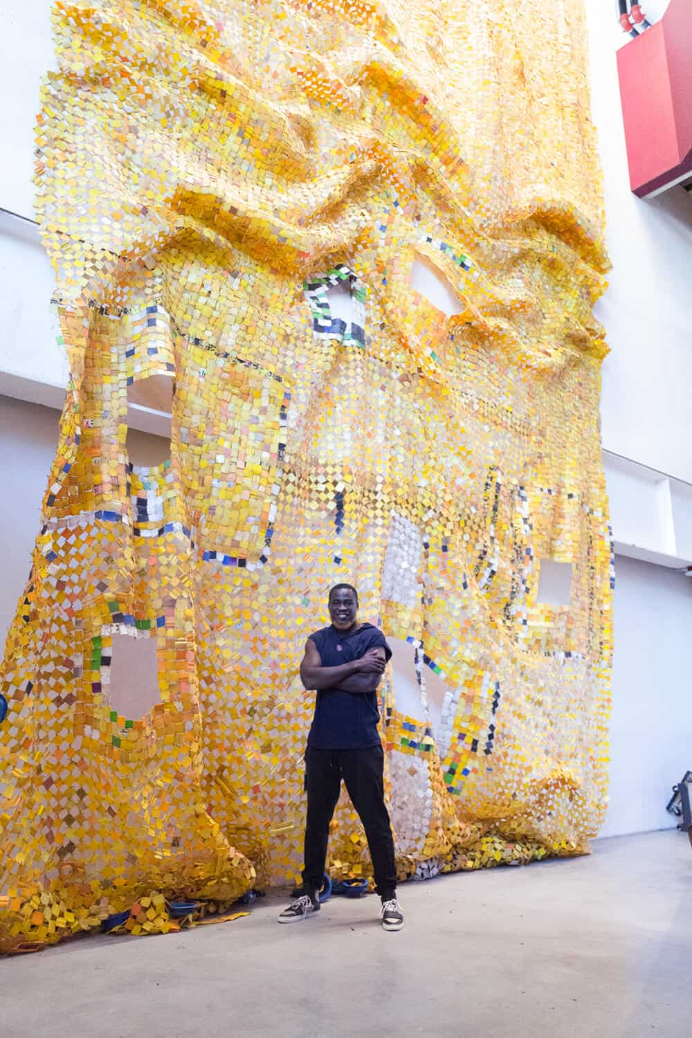 Serge Attukwei Clottey installing his work Kusum Gboo Ga (Tradition never dies) at the Facebook headquarters, 2018.