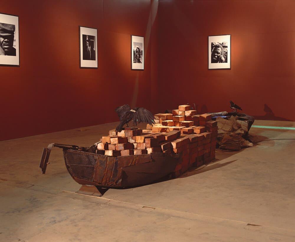 António Ole, Margem da Zona Limite, 1995. Eisen, Ziegel, einbalsamierte Vögel, Fotografie und Archive. 1. Johannesburg Biennale. Mit freundlicher Genehmigung des Künstlers.
