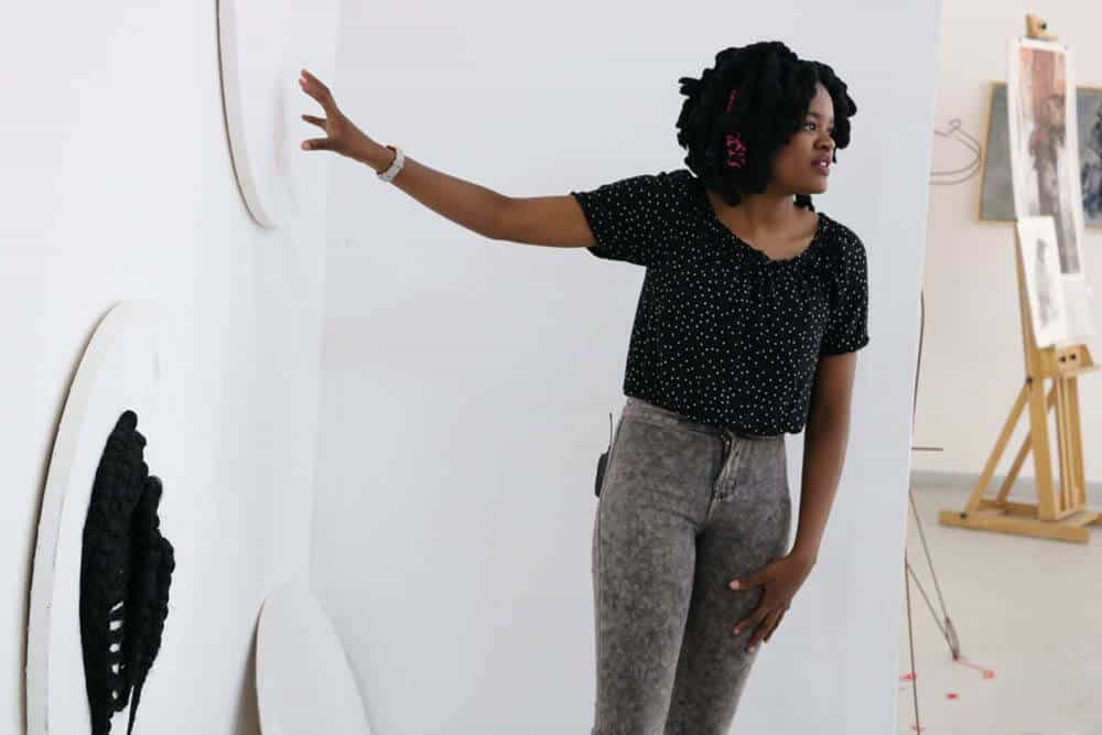 Lebohang Motaung explaining her work during a studio visit. Courtesy of The Project Space.