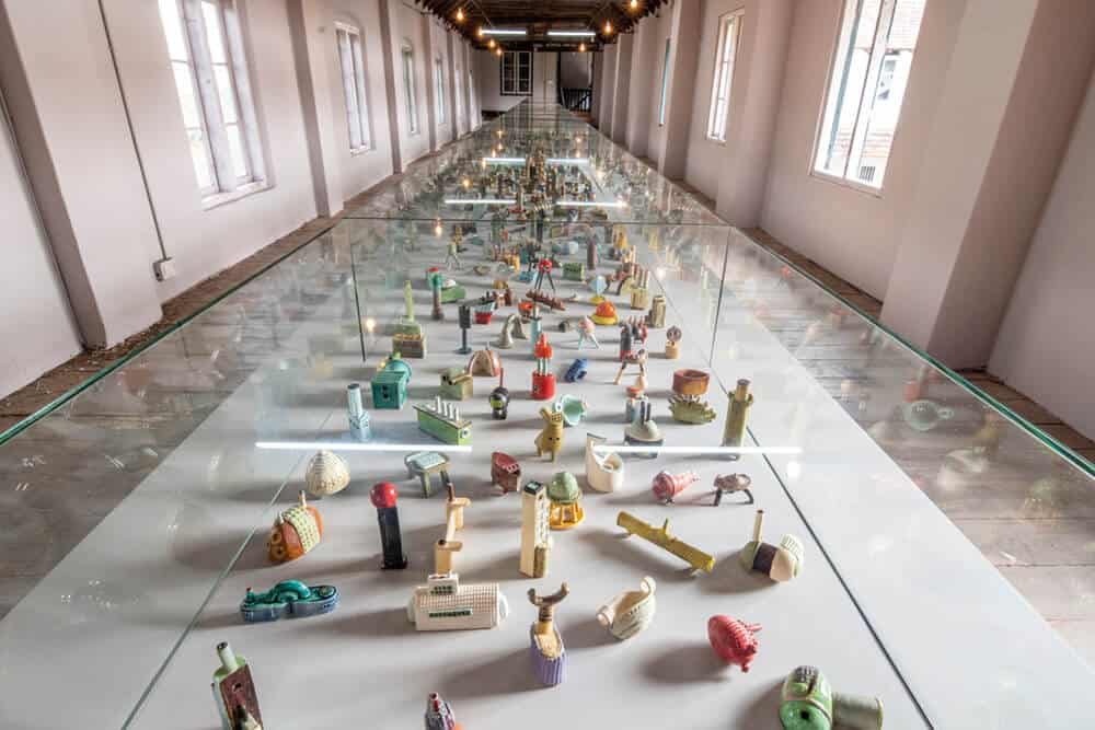 Lubna Chowdhury, 'Metropolis', Installation view at Kochi-Muziris Biennale 2018, Courtesy of Kochi Biennale Foundation. This multi-object work consists of over a thousand handmade clay sculptures presented in display cases. Lubna Chowdhury began Metropolis in 1991 and didn't complete the installation of 1000 ceramic sculptures until 2017, when she first exhibited the work in its entirety at the Victoria and Albert Museum in London.