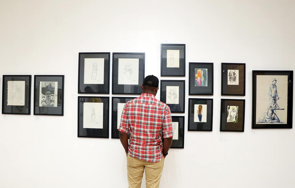 Ein Besucher, der das Ausstellungsdisplay betrachtet. GESICHTSSEITE: Folklore - Vogel und der Mann, 1968. Acryl auf Leinwand, 125 x 80.5 cm.