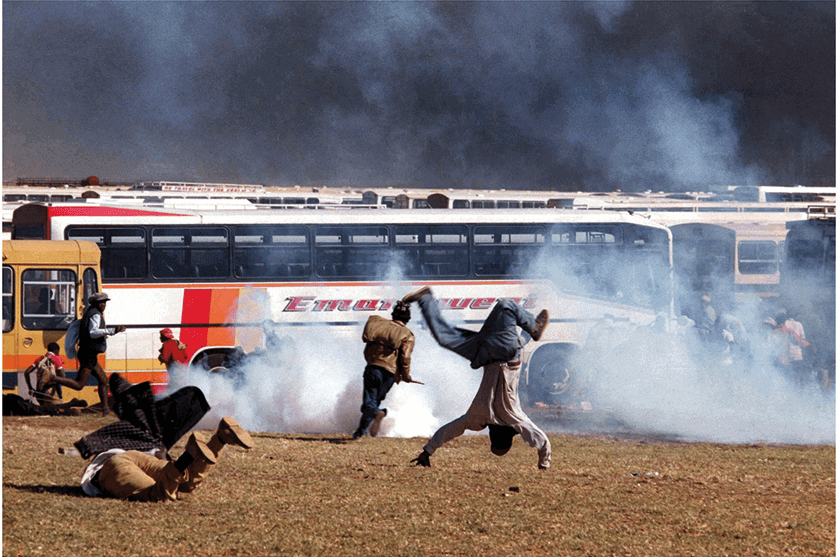 Somersault, Soweto, 1993. African National Congress and Communist Party supporters scatter as police fire teargas and live rounds outside the Soweto soccer stadium where the funeral of ANC and CP leader Chris Hani was attended by hundreds of thousands of mourners on 19 April.