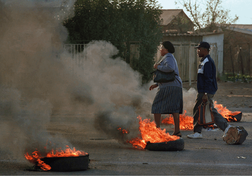 Work, Khumalo Street, 1990. A man and a woman walk through burning barricades to get to work. Thokoza is a small, nondescript township; the main road, Khumalo Street, runs north-south for four kilometres through an elongated triangle from one set of migrant workers' hostels to another. As the Hostel War cemented frontlines, Khumalo Street became a no-go area, though occasionally we would brave a run along it, sinking low into the car seats while racing through the stop signs and hoping no one would shoot.