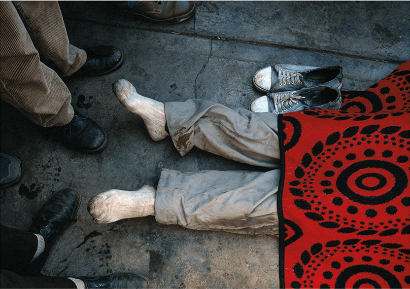 Shoes #2, Thokoza, 1996. Fellow combatants stand over the covered body of a young ANC Self Defence Unit member who was killed by Inkatha supporters. The young man's mother sat wrapped in a blanket on a chair watching over her son's body. Her face was set in a mask of anger and hatred. When a police detective came to the scene – a rare occurrence – she turned her venom on him, refusing to answer his questions. The SDU members also insulted him and told him to leave – no one expected any real policing to be done.