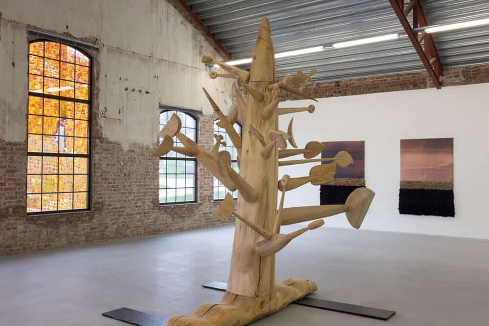 Installation view of Ibrahim El-Salahi, Meditation Tree, 2018. Lime wood, 10,5 ft (left). Courtesy of Vigo Gallery. Jöel Andrianomearisoa, Les Horizons Complexes (de l'Amour et d'une Romance) I, 2018. Textiles, 190 x 130cm. Les Horizons Complexes (de l'Amour et d'une Romance) II, 2018. Textiles, 190 x 130cm. Courtesy of the artist and Sabrina Amrani Gallery.