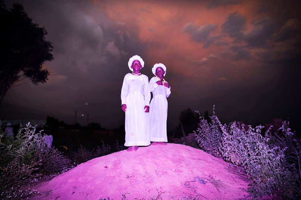 Sanne de Wilde & Bénédicte Kurzen, Nigeria, Igbo-Ora, October 2018. Twins stand a little monticule at the end of a celebration day at the Celestial Church on a rainy season afternoon. Igbo-Ora, the self proclaimed 'Twin Capital of the World' has earned its nickname by the unusually large number of twin births in the region. Research has suggested that the multiple births could be related to the (over)consumption of local crops by the women in the region of Igbo Ora. Although no direct relation between dietary intake and twin births has been proved, a research study carried out by the University of Lagos Teaching Hospital has suggested that a chemical found in Igbo-Ora women and the peelings of a widely consumed tuber (yams) could be causing twins births. Another possible explanation is genetics.