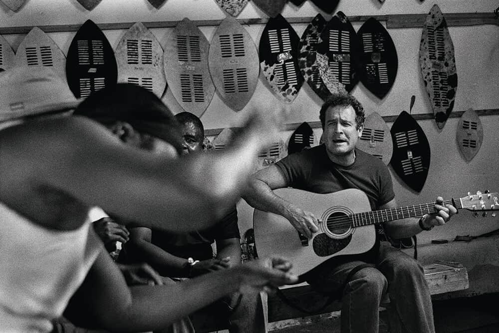 Johnny toca la guitarra en el estilo de púa tradicional zulú altamente sofisticado. © Patrick de Mervelec