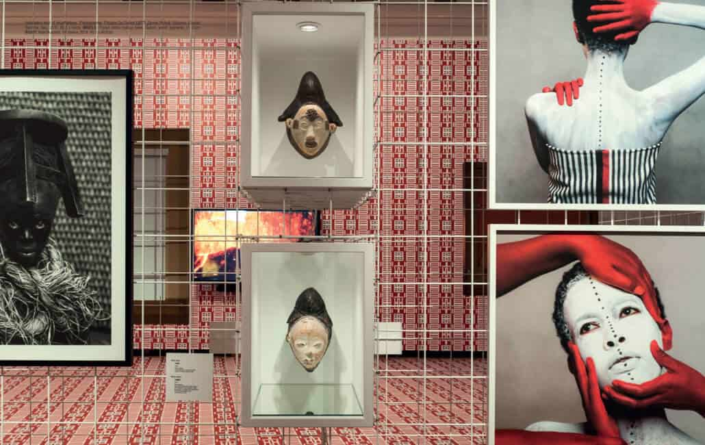Installation shot of 'incarNations'. Photographer: Philippe De Gobert LEFT: Zanele Muholi, Sibusiso, Cagliari, Sardinia, Italy, 2015, 69,5 x 94cm. MIDDLE: Punu/Lumbu mukuyi mask, Gabon, wood, pigments, H. 35cm. RIGHT: Aida Muluneh, 99 Series, 2014. 90,5 x 90,5cm.
